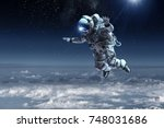astronaut floating above clouds | Shutterstock . vector #748031686