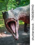 Small photo of Solec Kujawski, Poland - August 2017 : Life sized Allosaurus dinosaur statue in a forest