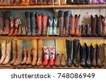 cowboy boots on a shelf in a store, facing straight - stock photo