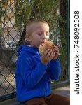 schoolboy eats cheeseburger boy ...   Shutterstock . vector #748092508