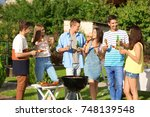 young friends having barbecue... | Shutterstock . vector #748139548