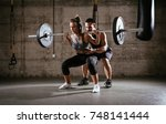 young woman doing squat... | Shutterstock . vector #748141444
