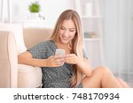 young woman using smartphone at ... | Shutterstock . vector #748170934