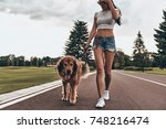 Stock photo good boy beautiful young woman walking with her dog while spending time outdoors 748216474