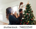 family decorating a christmas... | Shutterstock . vector #748222549