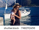 mother in the hat sitting with... | Shutterstock . vector #748292650