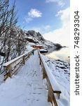 Small photo of Snow covered plank gangway leading to red rorbuer-wooden traditional fishing huts now for tourist use in the Vika area to the S.of Nusfjord fishing village. Flakstadoya-Lofoten-Nordland fylke-Norway.
