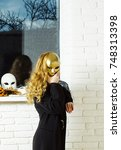 Small photo of Woman or girl cover face with golden mask with long blond hair at window. Carnival, masquerade, masque party, holiday celebration. Decoration, amusement, protection, disguise, pretense concept.