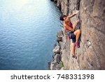 the girl climbs a climbing... | Shutterstock . vector #748331398