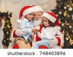 santa claus with kids indoors... | Shutterstock . vector #748403896