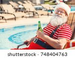 santa claus near the pool... | Shutterstock . vector #748404763
