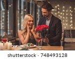 handsome elegant man is giving... | Shutterstock . vector #748493128