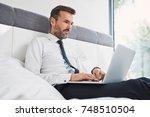 handsome businessman using... | Shutterstock . vector #748510504