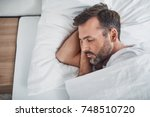 man sleeping peacefully in bed | Shutterstock . vector #748510720