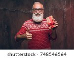 senior bearded man holding gift ... | Shutterstock . vector #748546564