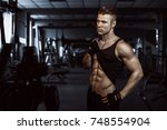 man sports in the gym.guy in... | Shutterstock . vector #748554904