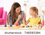 cute girl with mother painting... | Shutterstock . vector #748585384