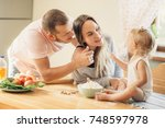 smiling young parents and their ... | Shutterstock . vector #748597978