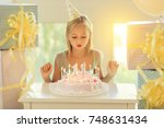 little birthday girl blowing... | Shutterstock . vector #748631434