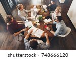group of creative managers sits ... | Shutterstock . vector #748666120