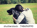 a woman with dog in the park. | Shutterstock . vector #748696990