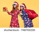 christmas. two young woman and... | Shutterstock . vector #748703230