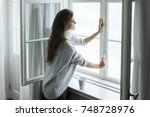 woman is opening window to look ... | Shutterstock . vector #748728976