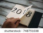 man flips notepad sheet on a... | Shutterstock . vector #748751038