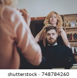 master cuts hair and beard of... | Shutterstock . vector #748784260
