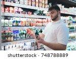 a man chooses a yogurt in the... | Shutterstock . vector #748788889