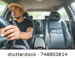 young man driving car carefully | Shutterstock . vector #748803814