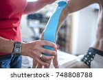 physiotherapist applying tape... | Shutterstock . vector #748808788