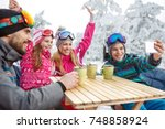 happy skiing family in cafe... | Shutterstock . vector #748858924