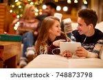 cheerful girl and boy listening ... | Shutterstock . vector #748873798