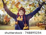 boy playing with autumn leaves... | Shutterstock . vector #748895254