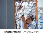 Small photo of Electrician trying to untangle wires in repair concept
