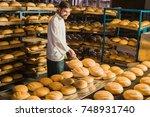 baker. bakery. a young handsome ... | Shutterstock . vector #748931740