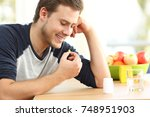 happy man taking a yellow omega ... | Shutterstock . vector #748951903