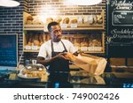 black man sells in bakery.   Shutterstock . vector #749002426