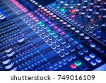 Professional sound and audio mixer control panel with buttons and sliders - stock photo
