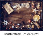 Small photo of Christmas gift, decorated gingerbread cookies, fried orange slices, nuts, cinnamon, anis on wooden tray, decorated by festive decor. Dark rustic style. Christmas Postcard concept.