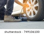 man checking air pressure and... | Shutterstock . vector #749106100