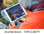 man navigating a flying drone... | Shutterstock . vector #749113879