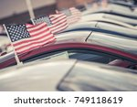 American Made Cars Sale Concept Photo. United States Economy and Market Theme. Brand New Vehicles For Sale with American Flags Attached. Dealership Lot. - stock photo