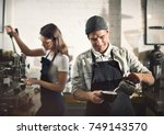 couple working in a coffee shop | Shutterstock . vector #749143570