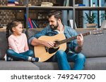 father playing guitar for... | Shutterstock . vector #749247700