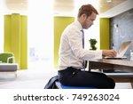 businessman using laptop in an... | Shutterstock . vector #749263024