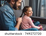 happy father making hair braid... | Shutterstock . vector #749272720