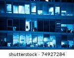 modern workplace through windows at night blue toned - stock photo