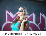 attractive girl on a wall... | Shutterstock . vector #749274334